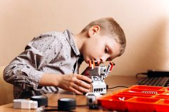 Boy dressed in gray shirt makes a robot from the robotic constructor at the desk in the School of Robotics royalty free stock photography
