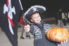 Boy dressed in Halloween pirate fancy costume with flag, pumpkin Royalty Free Stock Images