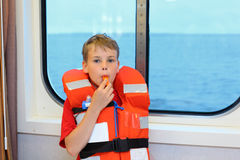 Boy dressed in life jacket blows whistle. And stands near window in cabin of ship stock images