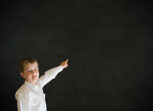 Boy dressed up as businessman pointing on blackboard background Royalty Free Stock Photography