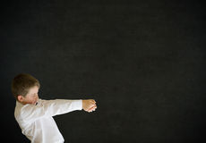 Boy dressed up as businessman pulling on blackboard background Royalty Free Stock Photo