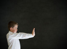 Boy dressed up as businessman pushing on blackboard background Stock Image