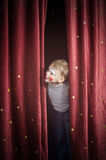 Boy Dressed Up as Clown Peeking Thru Stage Curtain. Young Blond Boy Dressed Up as Clown Peeking Out Through Opening in Red Stage Curtain as if Waiting for royalty free stock image