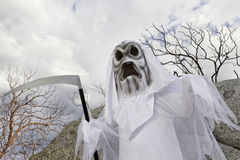 Boy dressed up as grim reaper holding scythe Stock Images
