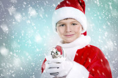 Boy dressed up as Santa in winter setting Stock Photo