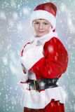 Boy dressed up as Santa in winter setting Stock Photography