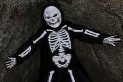 Boy dressed up as skeleton posing on rock Royalty Free Stock Photo