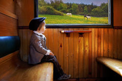 Boy, dressed in vintage coat and hat, sitting in a train Royalty Free Stock Photos