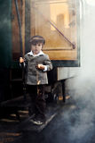 Boy, dressed in vintage coat and hat, standing on stairs of stea Stock Photography