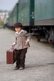 Boy, dressed in vintage coat and hat, with suitcase Royalty Free Stock Images