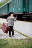 Boy, dressed in vintage coat and hat, with suitcase Stock Photos