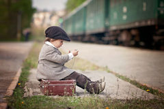Boy, dressed in vintage coat and hat, with suitcase Royalty Free Stock Photo