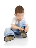 The boy dresses shoes. The little boy without assistance dresses shoes stock image