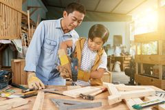 Boy drilling wooden planks royalty free stock image