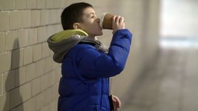 Boy drink hot coffee in the tunnel, waiting for someone, delay, winter. Have fun royalty free stock photos