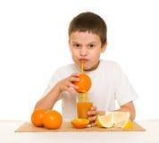 Boy drink orange juice with a straw Royalty Free Stock Photo