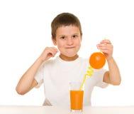 Boy drink orange juice with straw Royalty Free Stock Photography