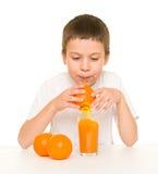 Boy drink orange juice with straw Royalty Free Stock Photos