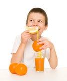 Boy drink orange juice with straw Royalty Free Stock Photo