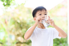 Boy drink water. Young Thai boy drinking water from glass in the garden Royalty Free Stock Photo