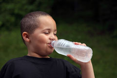 Boy drinking. Latino boy drinking water from bottle royalty free stock photos