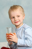 Boy drinking carrot juice Royalty Free Stock Images