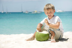 Boy drinking coconut juice on sea background Stock Photos