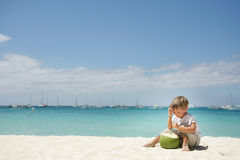 Boy drinking coconut juice on sea background Royalty Free Stock Photography