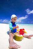 Boy drinking coconut water on tropical island beach. With blue lagoon Stock Image