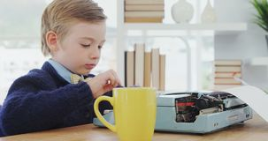 Boy drinking coffee while working on typewriter 4K 4k. Boy drinking coffee while working on typewriter in the office 4K 4k stock footage