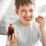 Boy drinking cough syrup Royalty Free Stock Images