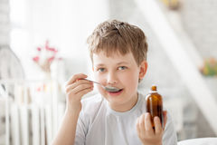Boy drinking cough syrup Royalty Free Stock Photo