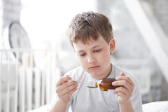 Boy drinking cough syrup Royalty Free Stock Image