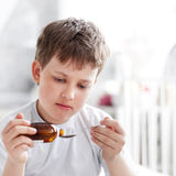 Boy drinking cough syrup. Indoors Stock Photos