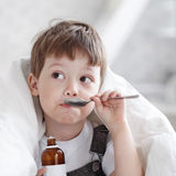 Boy drinking cough syrup Stock Images