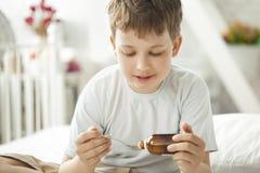 Boy drinking cough syrup Stock Photos