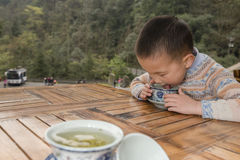 Boy drinking covered bowl tea Stock Images