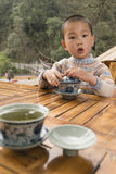 Boy drinking covered bowl tea Royalty Free Stock Images