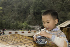 Boy drinking covered bowl tea Royalty Free Stock Photos