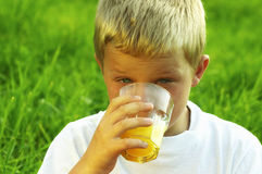 Boy drinking fresh orange juice Stock Images