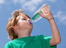 Boy drinking fresh water outdoors Stock Photos