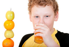 Boy drinking a glass of orange juice. On a white background Royalty Free Stock Image