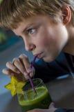 Boy drinking green smoothie Stock Photos