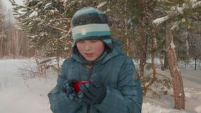 Boy drinking hot tea. Cute teenager drinking hot tea from the red teacup during his hiking walk in the winter forest stock video footage