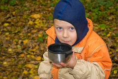 The boy is drinking hot tea outdoors. Boy drinks tea from a metal cup royalty free stock photos