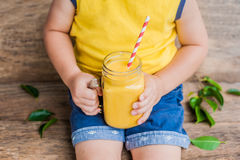 Boy drinking juicy smoothie from mango in glass mason jar with striped red straw on old wooden background. Healthy life concept, c Royalty Free Stock Photography