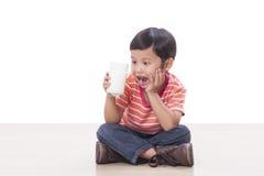 Boy drinking milk. Cute boy drinking milk on white Royalty Free Stock Photography
