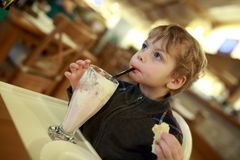 Boy drinking milkshake. At table in cafe Stock Images
