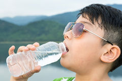 Boy drinking mineral water Stock Images
