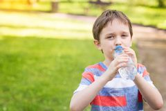 Boy drinking mineral water from the plastic bottle Royalty Free Stock Photo